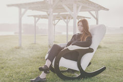 Beautiful happy woman relax in chair on lake morning Stock Photo
