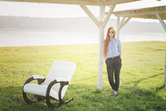 Beautiful happy woman relax in chair on lake morning Stock Images