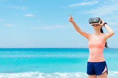 Beautiful happy woman runner wearing VR technology. Glasses watching 3D video and using hand pointing touching simulation when she workout on beach Stock Photography