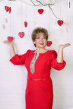 Beautiful happy woman of 50s in red dress. Valentine`s Day Stock Photo