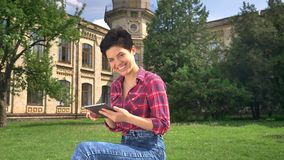 Beautiful happy woman with short black hair typing on tablet and smiling at camera, sitting in park near college stock video