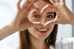 Beautiful Happy Woman Showing Love Sign Near Eyes. Healthy Eyes And Vision. Portrait Of Beautiful Happy Woman Holding Heart Shaped Hands Near Eyes. Closeup Of Royalty Free Stock Photography