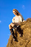 Beautiful happy woman siting on haystack Royalty Free Stock Photography