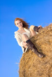 Beautiful happy woman siting on haystack Stock Image