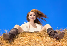Beautiful happy woman siting on haystack Royalty Free Stock Photo