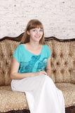 Beautiful happy woman sits on couch Royalty Free Stock Photography