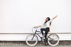 Beautiful happy woman sitting on bicycle and giving salute gesture. Copyspace royalty free stock photo