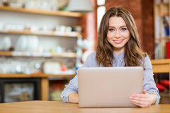 Beautiful happy woman sitting in cafe and using laptop Royalty Free Stock Photos