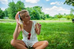 Beautiful happy woman sitting on the grass in summer stock image