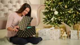 Beautiful Happy Woman Sitting Next To Christmas Tree With A Gift In Her Hands. Merry Christmas and New Year Concept. HD, Good Mood stock video footage
