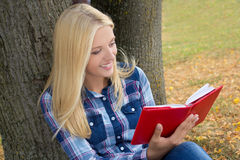 Beautiful happy woman sitting in park and reading book Stock Photos