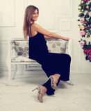 Beautiful happy woman sitting and posing on the bench in fashion Royalty Free Stock Photography