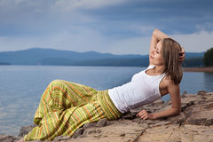 Beautiful happy woman sitting on rock over sea Royalty Free Stock Photo