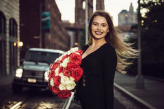 Beautiful happy woman smiling and holding luxury flower bouquet. Royalty Free Stock Images
