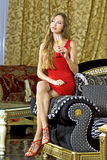 Beautiful happy woman on a sofa. Beautiful happy woman in red dress on a sofa with glass of champagne royalty free stock image