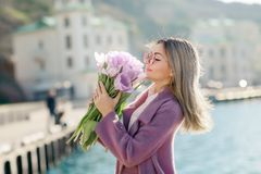 Beautiful happy woman with straight hair holding a bouquet of pink tulips one spring sunny day royalty free stock image