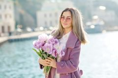 Beautiful happy woman with straight hair holding a bouquet of pink tulips one spring sunny day stock images