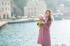 Beautiful happy woman with straight hair holding a bouquet of pink tulips one spring sunny day royalty free stock photo