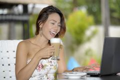 Beautiful happy woman in Summer dress outdoors at nice coffee shop having breakfast networking or working with laptop computer Stock Images
