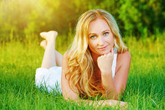 Beautiful happy woman in summer on nature lying on grass Royalty Free Stock Photo