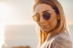 Beautiful happy woman in sunglasses standing at the sea, girl in grey coat royalty free stock photos