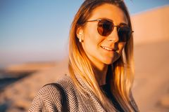 Beautiful happy woman in sunglasses standing at the sea, girl in grey coat royalty free stock images