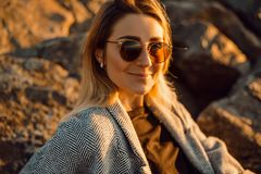Beautiful happy woman in sunglasses standing at the sea, girl in grey coat royalty free stock photography