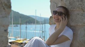 People on holiday in warm countries. Beautiful happy woman in sunglasses talking to someone on smartphone while on sea vacation on sunny summer day stock video footage