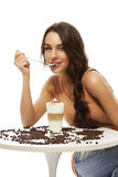 Beautiful happy woman at a table with latte  Royalty Free Stock Photos