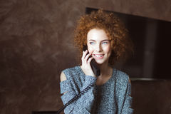 Beautiful happy woman talking on landline telephone in the room Royalty Free Stock Images