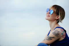 Beautiful happy woman with tattoo in glasses, place for your text stock image