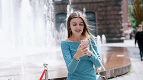 Beautiful happy woman using mobile phone and talking with friends by video call on the street stock footage