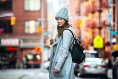 Beautiful happy woman walking on city street wearing casual grey coat and hat with a bag Stock Images