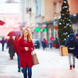 Beautiful happy woman walking on crowded city street in winter stock images