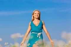 Beautiful happy woman walking on flower field Royalty Free Stock Image