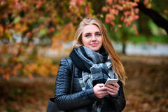 Beautiful happy woman walking and texting in the autumn park Stock Image