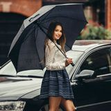 Beautiful happy woman walking under the rain with umbrella and smiling on city street Royalty Free Stock Photos