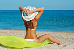Beautiful happy woman in white bikini with yellow inflatable mattress on the beach.  Royalty Free Stock Photos