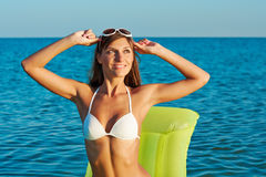 Beautiful happy woman in white bikini with yellow inflatable mattress on the beach.  Royalty Free Stock Photo