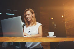 Beautiful happy woman working on laptop computer during coffee break in cafe bar Stock Images