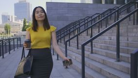 Asian business woman drinking coffee on the go. Beautiful happy young adult business woman in blouse and formal skirt walking in business city area with bag and