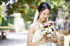 Happy asian bride with flowers. Beautiful and happy young asian bride wearing bridal veil holding a bunch of flower Stock Images