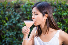 Beautiful happy young Asian woman enjoying a martini Stock Photography
