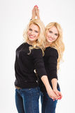 Beautiful happy young blonde sisters twins posing Royalty Free Stock Image