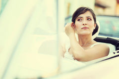Beautiful happy young bride looking from red retro auto car Stock Photo