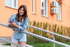 Beautiful happy young brunette woman in denim casual style standing on upstairs, holding her mobile smartphone and looking at stock photography