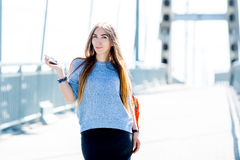Beautiful happy young businesswoman using cell phone on city street. Beautiful young businesswoman using cell phone on city street royalty free stock photography