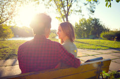Beautiful happy young couple enjoying nature. Dating young couple sitting in autumn park. Beautiful happy young couple enjoying nature Royalty Free Stock Photo