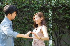 Beautiful happy young couple fun making gesture heart shape with hand outdoor together, stock photos