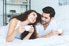 Beautiful happy young couple holding cups of coffee and lying. On bed royalty free stock photo